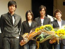 スペシャルゲストのK(一番左)より花束を受け取ったYUI、塚本高史、小泉監督